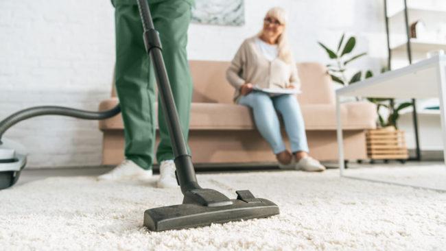 un assistente che aiuta una persona con le pulizie domestiche