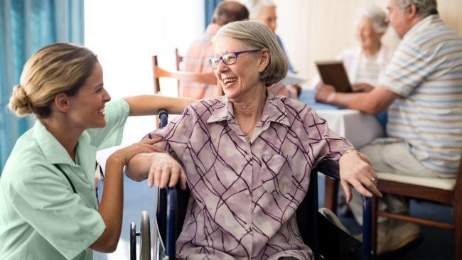 una persona anziana in casa di riposo in compagnia del suo assistente privato