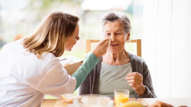 una persona anziana assistita da un'operatrice, in sostituzione della badante in ferie o in malattia