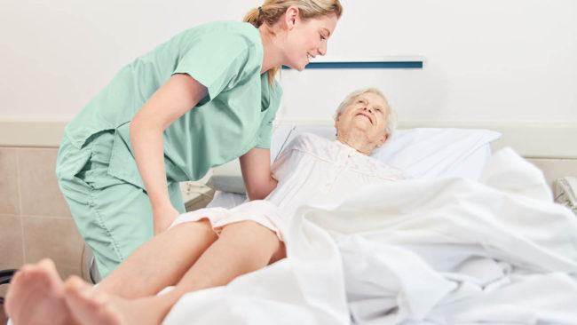 infermiera che aiuta una persona anziana a girarsi nel letto, per prevenire o curare le piaghe da decubito